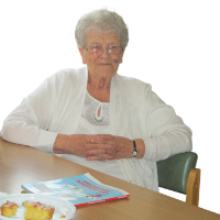 Diana (an elderly lady) is sitting in her chair smiling at the camera.