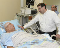Reagan is lying in his hospital bed talking to an advocate.