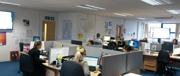 POhWERs information and advice centre. Lots of people are sitting at their desks with headsets on.