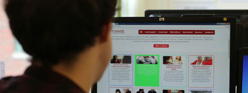 A picture of a man sitting in front of a computer monitor looking at the new POhWER website.