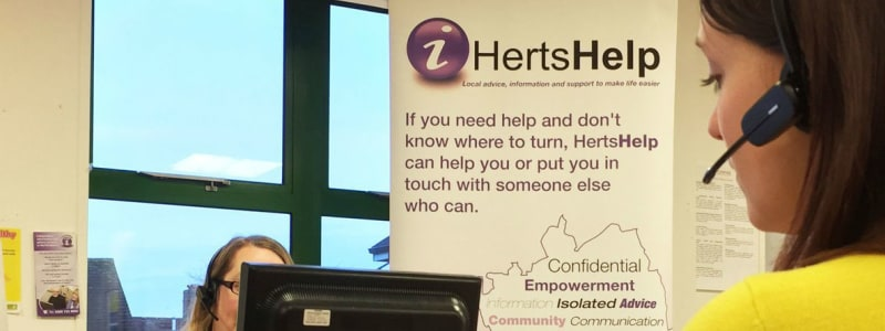 two Herts Help staff sitting at their desks on the phone to clients.