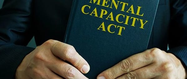 Person holding a book of the Mental Capacity Act